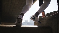 4K Male athlete climbs up a wall and soaks in the city view in the sunlight Stock Footage