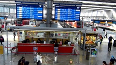 People at an information desk inside Munich central train station Stock Footage