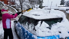 The girl clears her car from snow Stock Footage