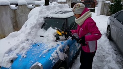 Girl clear her mini cooper from the snow Stock Footage