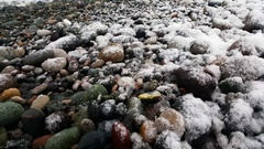 Wet snow falling on sea pebbles Stock Footage