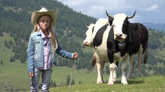 4K Cowherd Child Pasturing Cows in Mountains, Shepherd Girl with Cattle on Grass Stock Footage