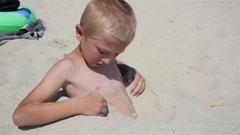 Boy buried in sand Stock Footage