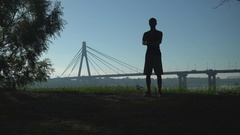 A silhuette video of a sportsman warming up for training on the nature Stock Footage