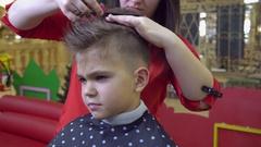 Children barber in beauty salon with little boy Stock Footage