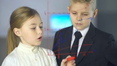 The girl discuss a graph near boy. Business and science concept with children Stock Footage