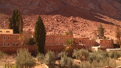 The building and the olive grove on the slopes barren mountains Stock Footage