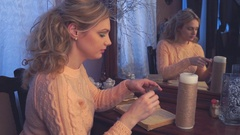 A girl lights a candle with a match Stock Footage
