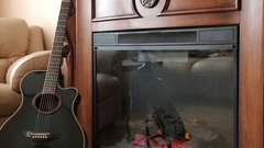 The guitar next to the fireplace Stock Footage
