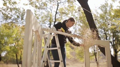 Wedding decorator decorates wedding arch in the form of doors in nature in a Stock Footage