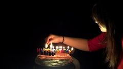 Mother lighting up birthday candles cake, son looking anxious, black background Stock Footage