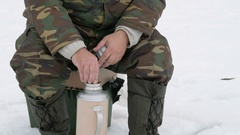 A man fishing on the lake in winter and drinking tea from a thermos. He eats Stock Footage