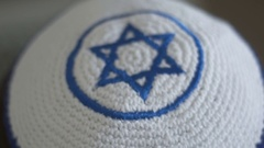 White kippah with blue Magen David on a head, a attribute of Judaism and Zionism Stock Footage