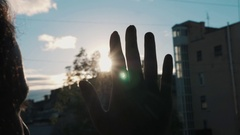 Slowmotion close up silhouette of palm hand blocking bright sun light outside Stock Footage