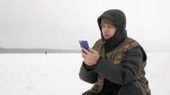 Young man on a frozen lake with a phone looking for the desired route Stock Footage