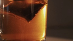 Slowmotion close up tea bag pulled and twitched in transparent glass of water Stock Footage
