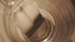 Close up slowmotion tea bag being putting in transparent glass cup Stock Footage