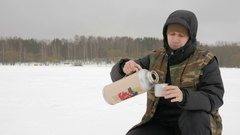 Young man on the frozen lake pours hot drink from a thermos. Very cool place Stock Footage