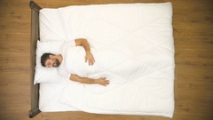 The sleeping man lay on the bed and yawn. Real time capture. View from above Stock Footage