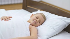 The sleeping boy lay on the bed and yawn. Real time capture Stock Footage