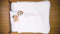 The boy lay on the bed with ball. Real time capture. View from above Stock Footage