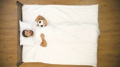 The sleeping man with ball dream on the bed. Real time capture. View from above Stock Footage