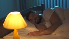 The unhappy man lay on the bed and turn off the lamp. Real time capture Stock Footage