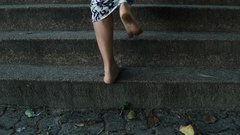Barefoot legs of Caucasian woman stepping up on stone stairs, close-up view Stock Footage