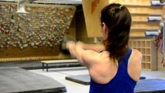 Kettlebell swings by athletic woman, rear shot. Stock Footage