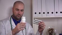 Handsome caucasian doctor pills in hand medication drops jar medical advice 4K  Stock Footage