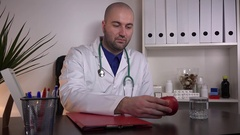 Male doctor medical uniform stethoscope showing red apple fruit to camera health Stock Footage