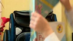 A schoolboy gathers in the morning to school backpack with textbooks Stock Footage