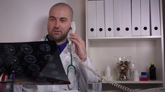 Handsome caucasian doctor with stethoscope in hospital phone call landline X ray Stock Footage