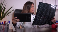 Confident young female medic working in office with x ray and tablet health care Stock Footage