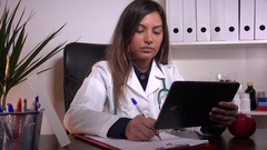 Young female doctor practitioner with tablet writing on clipboard medical news  Stock Footage