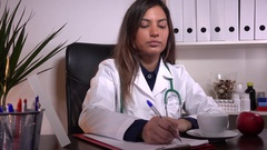 Beautiful young latina doctor drinking morning coffee tea work hospital activity Stock Footage