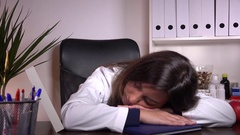 Overly tired exhausted overworked woman doctor sleeping desk consulting office  Stock Footage