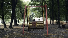 Girl swinging on the swing with his back to the viewer Stock Footage