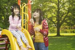 Beautiful mother and child play bubbles Stock Photos