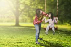 Cute child and young mother playing swing Stock Photos