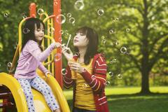 Cute child and mother blowing soap bubbles Stock Photos