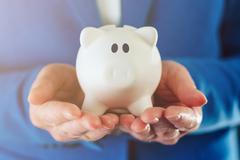Piggy coin bank in hands of businesswoman Stock Photos