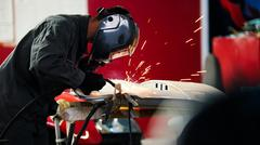 Welding industrial: worker in helmet repair detail in car auto service Stock Photos