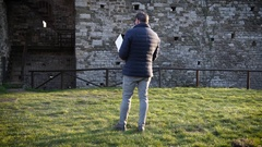 A man dressed in the down jacket pilots his drone near an ancient towe.. Stock Footage