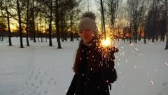 Girl enjoy burning sparkler stick, stay at dusk winter park, show to camera Stock Footage