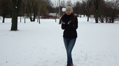 Cheerful woman play snowball game, turn and throw, successfully hit camera Stock Footage