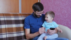 Father And Son Using Smart Phone Together Stock Footage