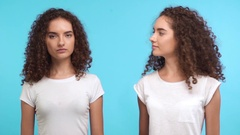 Two beautiful young curly female twins touching each other hair smiling with Stock Footage