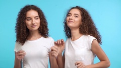 Two beautiful Caaucasian female twins with curly hair and white t-shirts dancing Stock Footage
