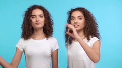 Two beautiful female curly Caucasian twins in white t-shirts synchronously Stock Footage